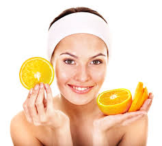 Woman holding up oranges for vitamin C for skin