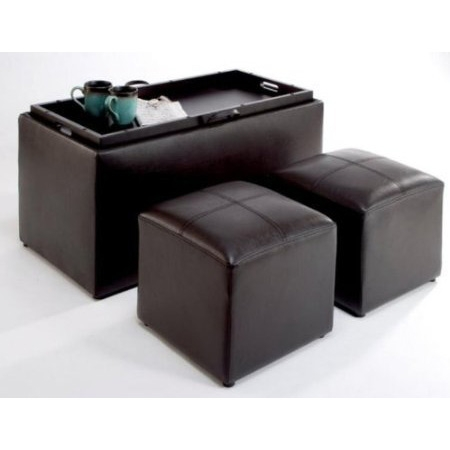Bench, coffee table, living room storage, and two footrests all packed into one, this Faux Leather Storage Bench Coffee Table with 2 Side Ottomans has it all. The bench offers the perfect storage compartment for throw blankets or board games, while also serving as a comfy seat. Espresso-finished faux leather upholstery with box stitching adorns the bench for a sleek appearance while resisting stains in high traffic areas. Inside the bench, two matching small ottomans are provided to rest tired feet, or serve as occasional stools. The underside of the bench's removable lid contains a built-in tray for a hard surface for supporting drinks or snacks; users can transport the tray using its two cut-out handles. Fully assembled upon shipping. Hardwood tray built into underside of bench lid.