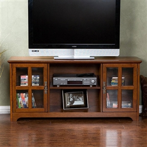 This Mission Oak TV Stand - Fits up to 50-inch Flat Screen TV features a rustic charm with a contemporary style with tempered glass doors. This stand fits up to a 50-inch flat panel TV and showcases a beautiful oak finish. Large center storage and glass paned side storage areas are each enhanced with an adjustable shelf for versatility; Center space is complete with a centered hole for cord management in the back; Tempered glass doors.Assembly Required.