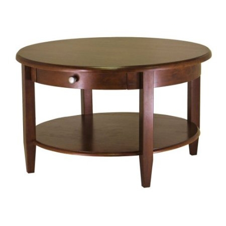 Clean, classic lines and a rich Antique Walnut finish make this Circular Wood Coffee Table with Bottom Shelf and Drawer a fine addition to a formal living room or well-tailored den. The roomy 30-inch top features gently rounded edges and perches on a simple apron with a concealed storage drawer. Below, the bottom shelf makes a nice display space for magazines, oversized books, or collectibles. Crafted of solid wood with a chrome-colored pull, the table is designed to be durable and sturdy as well as handsome. It stands 18 inches high; assembly is required.