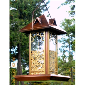 "Metal and Glass Bird Feeder with Antique Copper Finish, PHRBF69:  This Metal and Glass Bird Feeder with Antique Copper Finish makes watching the feeder as much fun as watching the birds. Made to our high standards of metal with an antique-copper finish - for durability and good looks. The glass seed container outlasts plastic, and is accented by solid brass trim. To easily fill or clean the feeder, simply remove the roof. Solid metal construction with antique copper finish and solid brass trim. Take advantage of this great deal today. 9""W x 14""H with additional high hanger. The glass seed container outlasts plastic, and is accented by solid brass trim,"