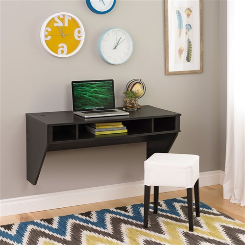 """Optimize your space with this Contemporary Space Saver Floating Style Laptop Desk in Ebony. Perfectly suited for any home office, den, living room, kitchen or bedroom. The stable work surface is ideal for any computer or simply as a place to get your work done. A rear """"flip-up"""" door conceals a storage compartment that is ideal for power bars and adapters. No more messy wires cluttering up your workspace! Installation is a breeze for this wall mounted desk with this innovative hanging rail system. Proudly manufactured in Canada using CARB-compliant, laminated composite wood. Ships Ready to Assemble, includes an instruction booklet for easy assembly and has a 5-year manufacturer's limited warranty."""
