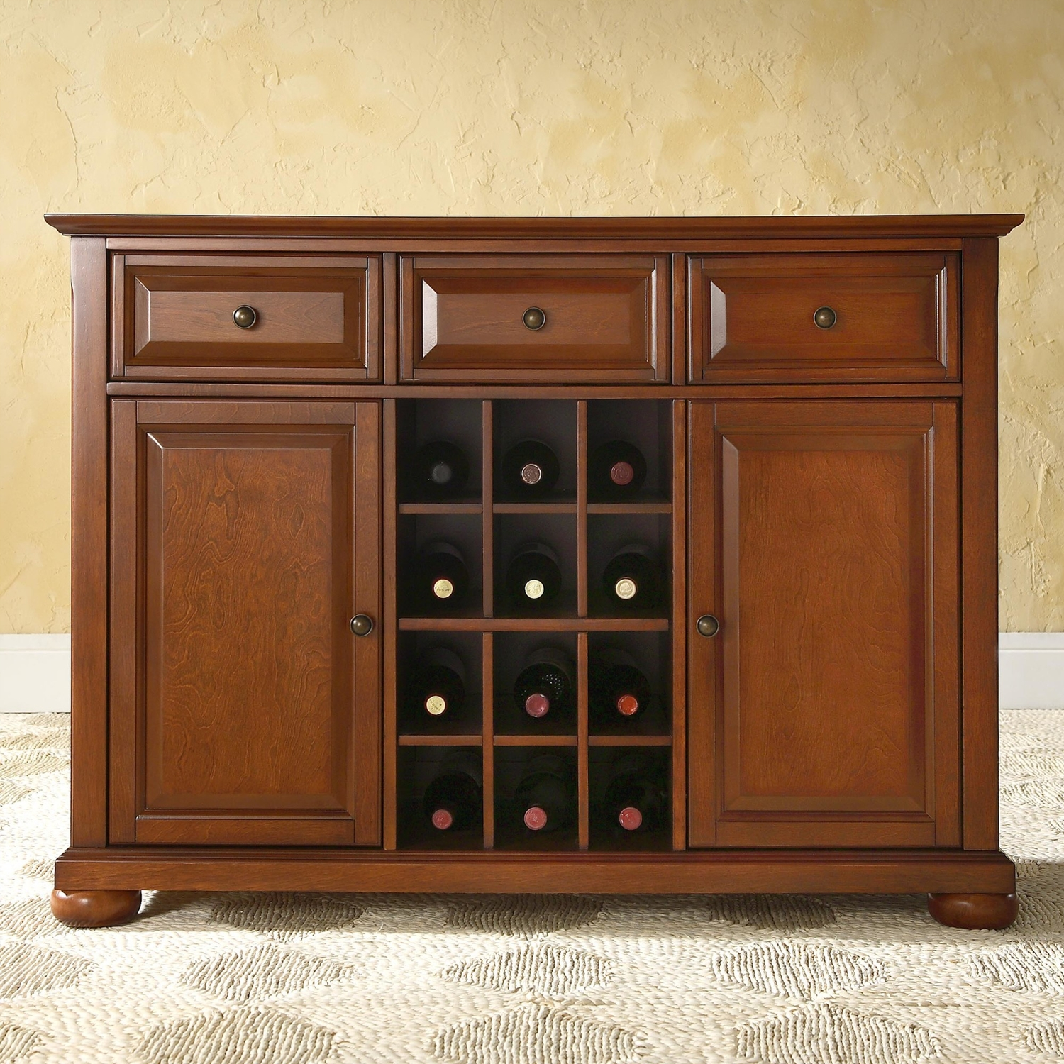 This Cherry Wood Dining Room Storage Buffet Cabinet Sideboard with Wine Holder merges clean modern lines and traditional raised panel doors to create a strong, solid place to store and display your favorite serving pieces. Three deep drawers sit just below the server's top, which can be used to store silverware, linen napkins, wine bottle openers and more. The stunning open air center storage area was designed for versatility. The dividers allow you to store up to 12 standard bottles of wine. They can also be removed to create two open shelves to display your favorite serveware. The legs boast adjustable levelers, for maximum stability. The fully finished back allows you to place this against a wall or in the open and still look magnificent from all angles. Product Care: Use a soft clean cloth that will not scratch the surface when dusting. Use of furniture polish is not necessary. Should you choose to use polishes, test in an inconspicuous area first. Use of solvents of any kind may damage your furniture's finish. To clean, simply use a soft clean cloth moistened with lukewarm water, buff with a dry soft clean cloth. Adjustable shelf behind each door; Adjustable levelers in legs; ISTA 3A certified; Constructed of solid hardwood and veneer; Center storage area can hold up to 12 wine bottles; Manufacturer provides a 90 day warranty against defects in material and workmanship; Product Type: Server; Number of Drawers: 3; Number of Cabinets: 2; Number of Interior Shelves: 4; Number of Doors: 2; Wine Rack Bottle Capacity: 12; Assembly Required: Yes; Product Warranty: 90 Day limited warranty.