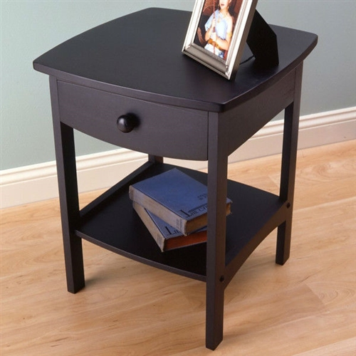 Bedeck your contemporary interiors with this Black 1-Drawer Bedroom Nightstand Contemporary End Table. Simple yet graceful, this nightstand is made out of manufactured wood for strength and durability. Flaunting delicate curves and four straight feet, this nightstand is available in a variety of finishes to choose from. It features one spacious drawer with wooden glides and safety stops that can be used to keep anything from handy utilities to bedtime essentials. This also has a small open shelf at the bottom, which can accommodate your books or magazines. Wipe this nightstand with a clean, dry cloth to keep dust and grime away. Top Finish: Polyurethane; NonToxic: Yes; Country of Manufacture: Thailand.