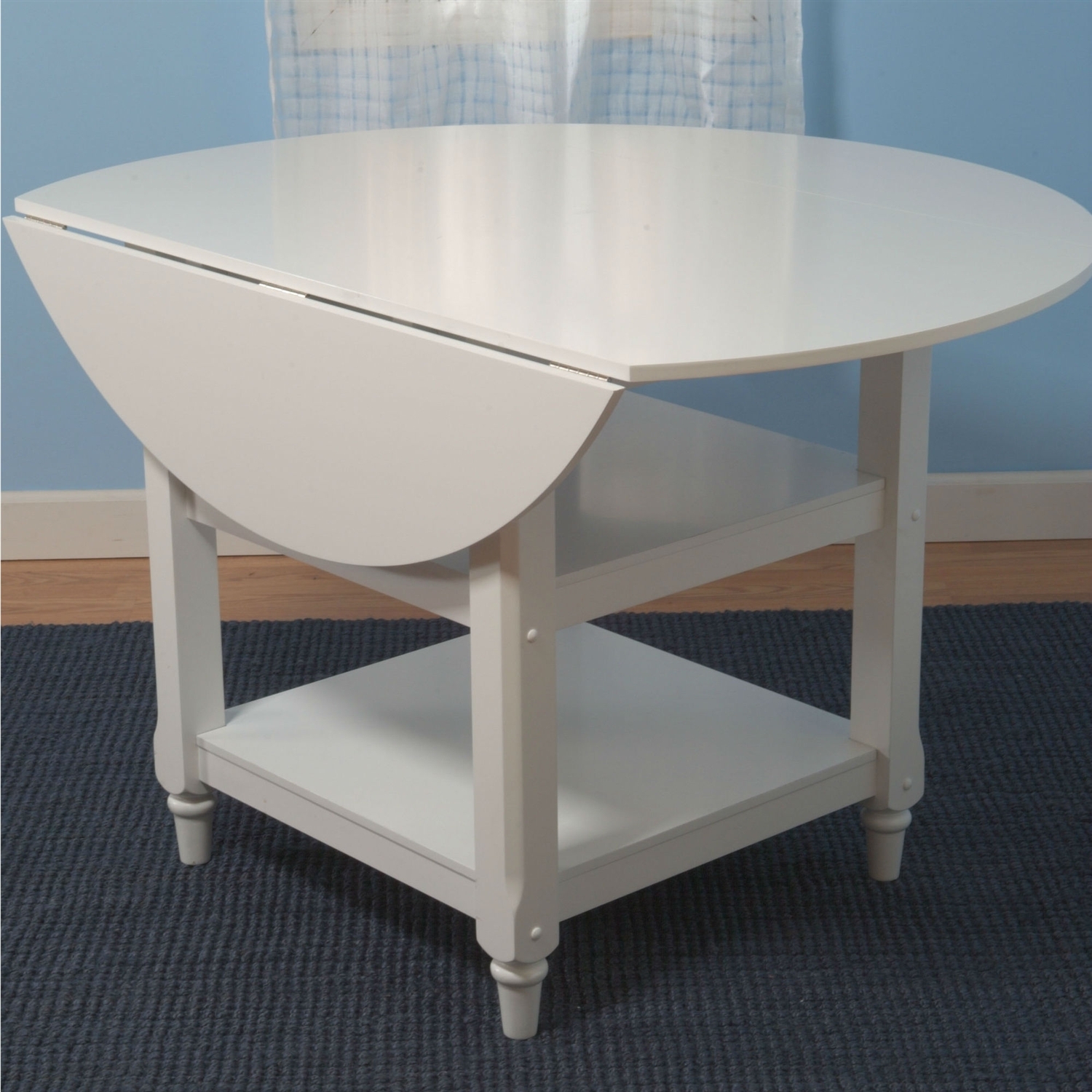 This 48-inch Round Dual Drop Leaf Dining Table in White Wood Finish would be a great addition to your home. It has a country style and is made of non-toxic wood. Assembly Required: Yes Top Material: Wood; Base Material: Wood Non-Toxic: Yes; Seating Capacity: 4 Table Base Type: Four leg; Product Care: Wipe clean with a dry cloth.
