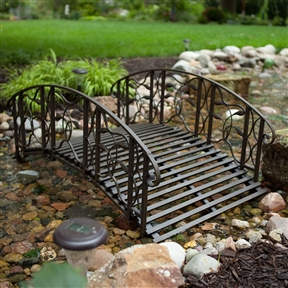 4-Foot Steel Frame Metal Garden Bridge in Rustic Weathered Black Finish, CMGB5187741 :  Like a small portal into a more romantic era, this 4-Foot Steel Frame Metal Garden Bridge in Rustic Weathered Black Finish instantly adds magic to your garden space. Use it as a traditional bridge to cross a small stream or simply to add visual interest, either way this bridge is something special. It's beautifully designed of sturdy steel, lavishly decorated with vines and leaves, and features a durable finish. The plank style walk enhances the look and provides secure footing in any weather.