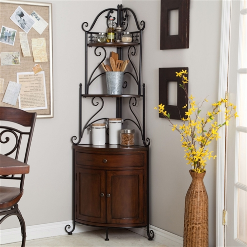 This Corner Bakers Rack with Wrought Iron Frame and Wood Storage Shelves is the perfect way to back your kitchen clutter into a corner. This quaint bakers rack has a solid pine base with wood shelves in a rich cherry finish. The wrought iron frame is protected by a powder-coated black finish and features an ornate country design. 1 drawer, 2 enclosed shelves, 2 open shelves; Style Traditional.