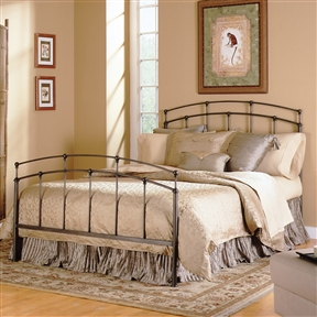 Like a treasured find in an old farmhouse or grandma's attic, this Queen size Metal Bed with Headboard and Footboard in Black Walnut combines sweet simplicity and sturdy elegance. This lovely design features open headboard and footboard grills lined with mixed-length rails that work together to support a double top arch. The wider corner posts along with the round finials, joints, and feet lend a substantial feel, while the narrower accent rails keep the look delicate and airy. Available in several finishes to complement any room's color scheme, this Black Walnut version showcases a two-tone blend of deep mocha brown with distressed black highlights for a rich, bold statement. A final coat of clear lacquer adds a bit of sheen and maintenance-free durability. The queen-sized model measures approximately 61-1/4 inches wide by 85 inches long. The headboard stands 49-5/8 inches high, and the footboard stands 34-1/4 inches high. Fashion Bed Group backs the bed with a 10-year limited warranty.