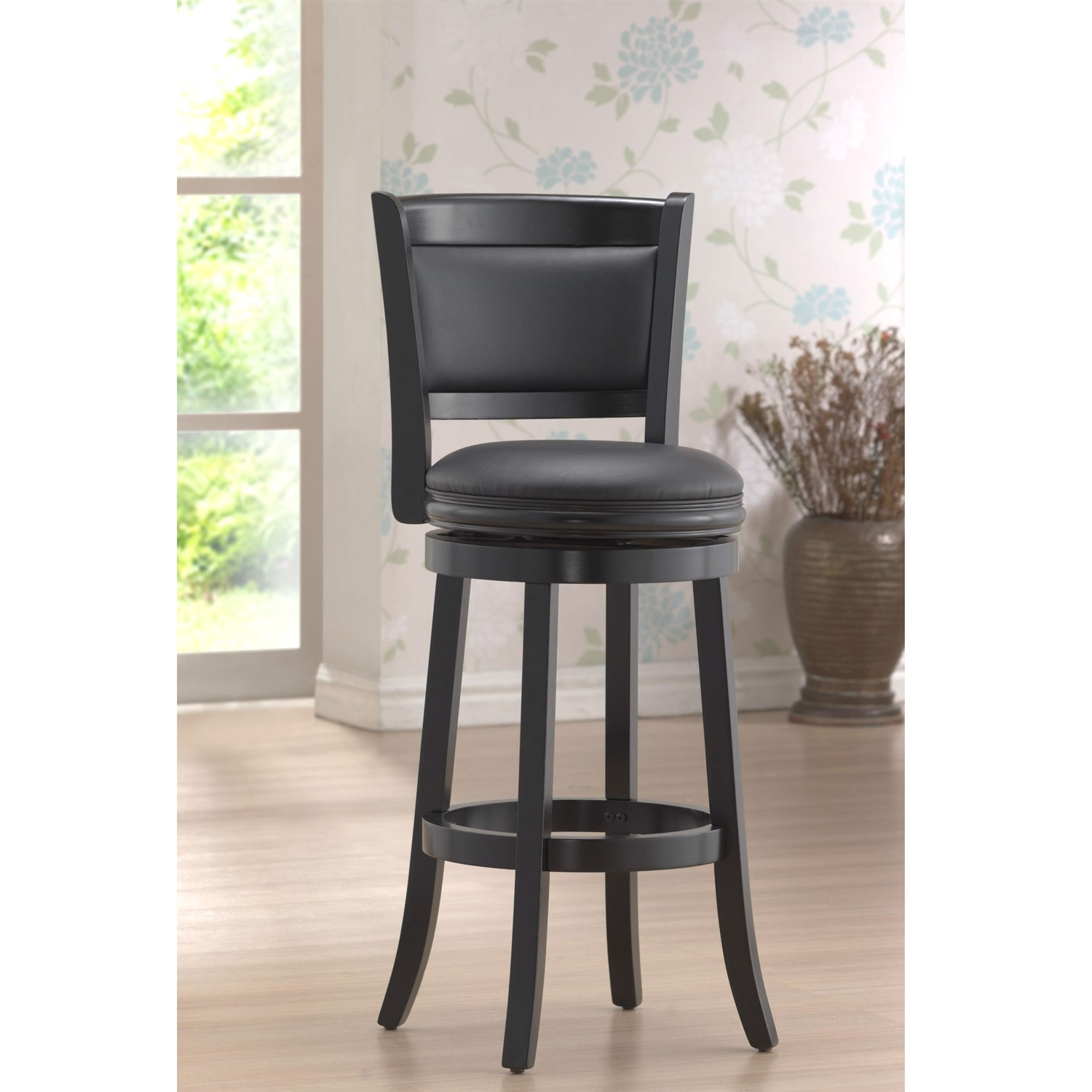 Accent your bar space with this classy and stylish Black 29-inch Swivel Seat Barstool with Faux Leather Cushion Seat. Its attractive and durable design is a perfect fit for all decor settings. It occupies less space and proves highly useful when you have guests at home.This stool has a solid hardwood construction that ensures it lasts for many years to come. The lustrous finish lends it a timeless look and adds to the appeal. It is fitted with a rich faux leather seat with high density foam to offer comfortable seating and enhance its appearance. It has flawlessly crafted French style legs with tempered bottoms. The steel ball bearings keeps it steady. The swivel ensures unrestricted movement. While the full ring footrest lends more strength and stability. The back support makes the seating experience more relaxed.The bar stool has a weight capacity of 250lbs. Its seat height is 29''. The overall dimensions of the bar stool are 43.5'' in height, 17'' in width and 18'' in depth. It is available in different shades to best suit your decor. This stool is best paired with an elegant bar table to complete the sophisticated look of your decor.