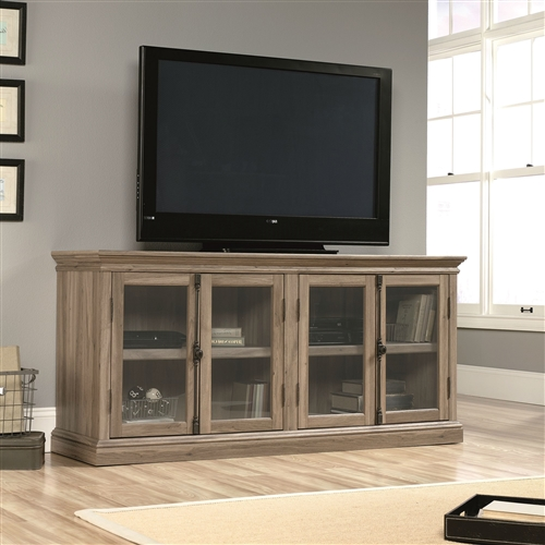 This Salt Oak Wood Finish TV Stand with Tempered Glass Doors - Fits up to 80-inch TV has two glass door cabinets with a spacious top. The glass door cabinets have two shelves each for storing your necessary items. You can place your decorative items like showpieces, books, flower vase or your media components like DVD player, CDs, or any audio video equipment. The top has an embossing effect that makes it look prettier. The cabinets have safety tempered glass door inserts on the wooden frame. The adjustable shelves in the cabinet give you space to arrange the shelves as per your usage requirements. The doors have metallic oval shaped knobs for better grip and easy functionality. The enclosed back panel gives you space to manage your cable wires and keep your room clutter free.