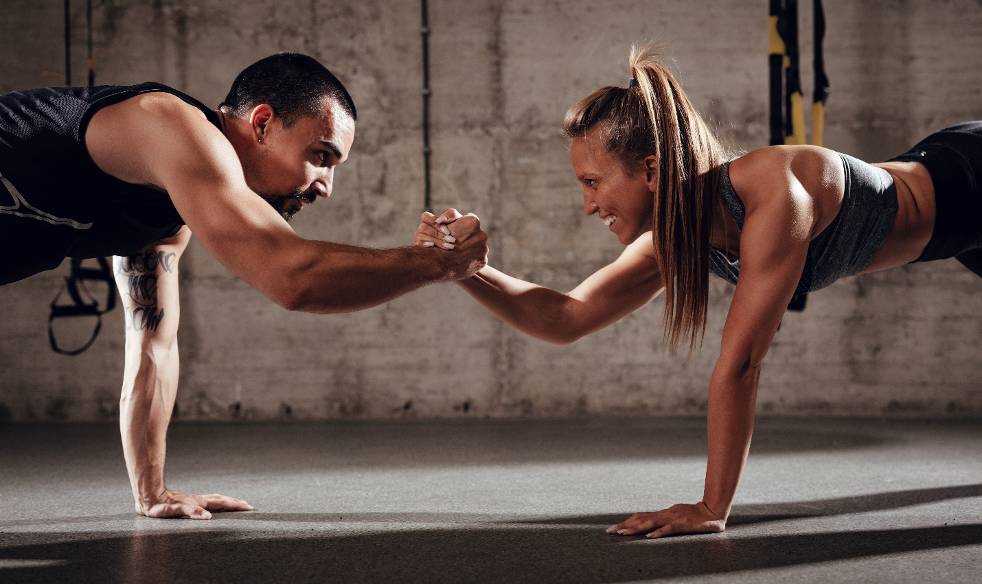 young muscular couple doing strength exercise work