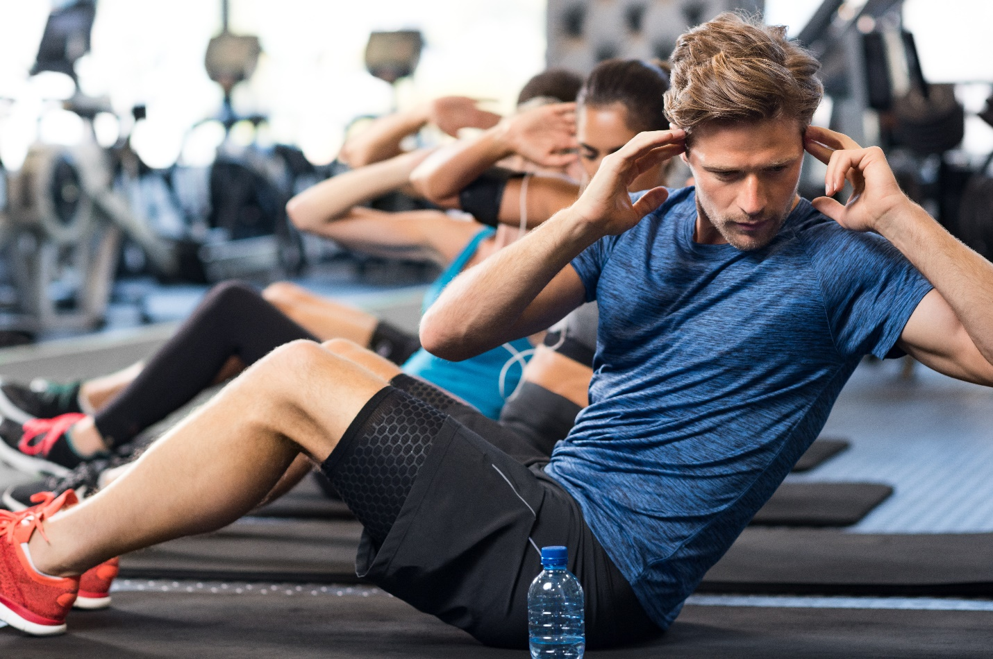 muscular guy doing sit ups at gym with other peopl