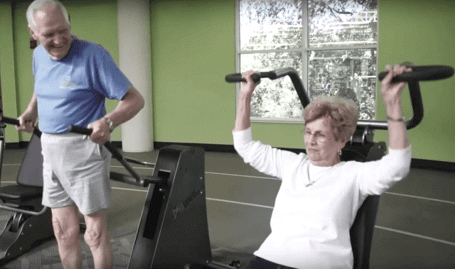 elderly man and woman exercising on equipment